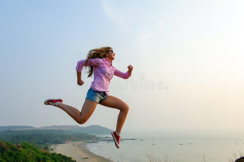 La bella giovane bruna felice salta massimo e fa i movimenti dinamici La ragazza sportiva in camicia, mette e scarpe da tennis immagine stock libera da diritti