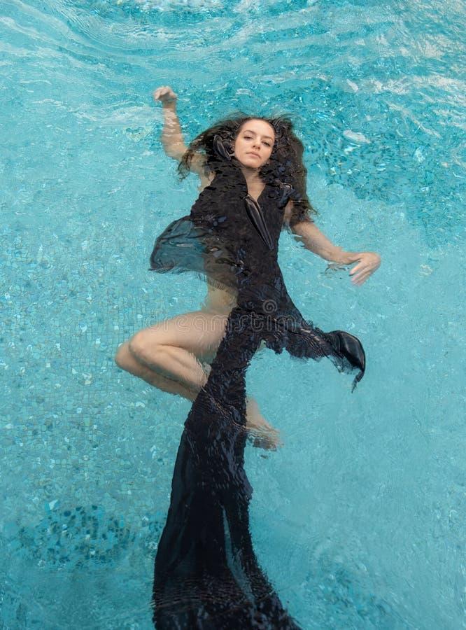 La bella giovane bruna rilassata in vestito nero, il capo, asciugamano fa galleggiare felicemente il galleggiamento nello stagno immagini stock