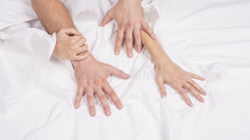 La bella giovane coppia sensuale sta facendo sesso sul letto Mano femminile che tira gli strati bianchi nell'estasi, orgasmo Conc immagine stock libera da diritti