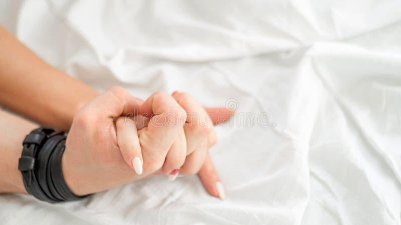 La bella giovane coppia sensuale sta facendo sesso sul letto Mano femminile che tira gli strati bianchi nell'estasi, orgasmo Conc immagini stock