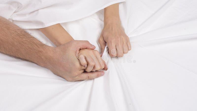 La bella giovane coppia sensuale sta facendo sesso sul letto Mano femminile che tira gli strati bianchi nell'estasi, orgasmo Conc fotografie stock