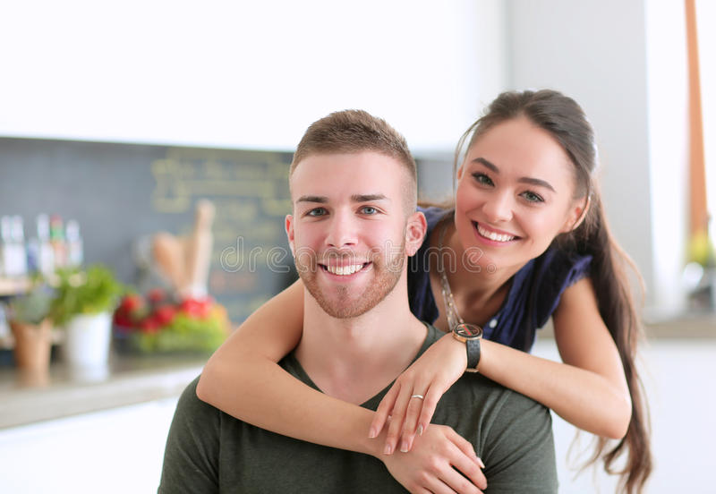 La bella giovane coppia sta divertendosi in cucina a casa fotografia stock libera da diritti