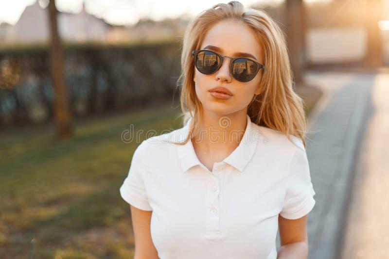 La bella giovane donna alla moda dei pantaloni a vita bassa in occhiali da sole d'avanguardia in una maglietta bianca di polo sta fotografie stock libere da diritti