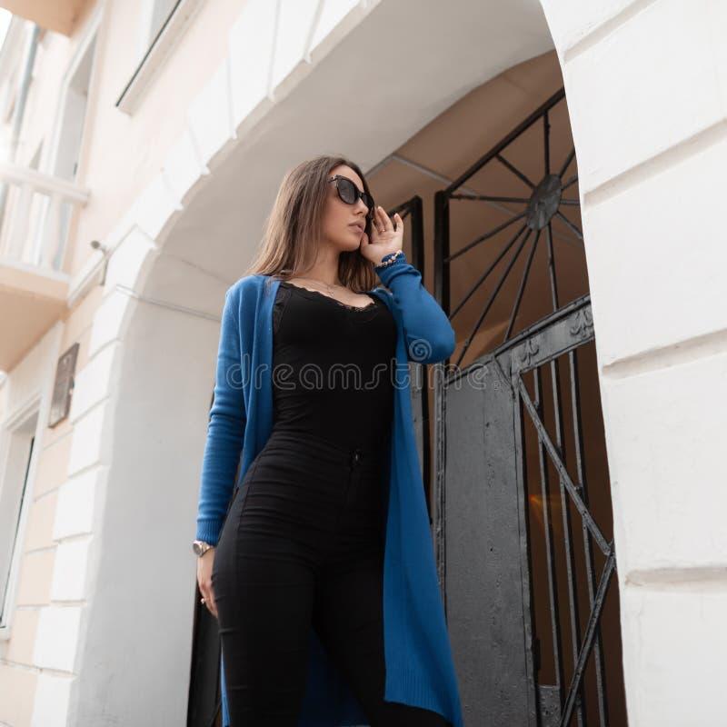 La bella giovane donna alla moda dei pantaloni a vita bassa in occhiali da sole in una maglietta nera in un capo tricottato dell' fotografie stock