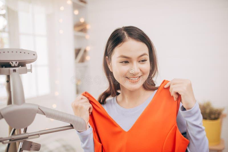 La bella giovane donna asiatica che sorride con i vestiti che provano sopra si agghinda adattarsi con moderno nella stanza fotografie stock libere da diritti