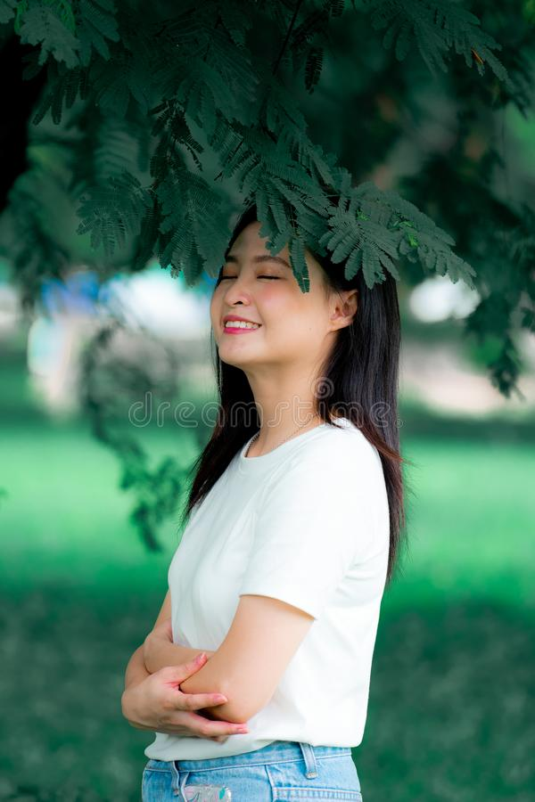 La bella giovane donna asiatica cinese deve godere di di rilassarsi nel verticale verde del ritratto del fondo della natura immagine stock libera da diritti
