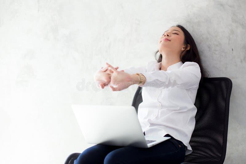 La bella giovane donna asiatica con l'allungamento del computer portatile e l'esercizio si rilassano dopo successo del lavoro immagine stock libera da diritti