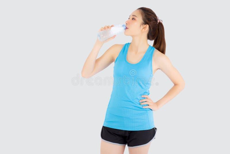 La bella giovane donna asiatica misura l'acqua potabile di forma dopo l'allenamento e l'esercizio isolata su fondo bianco fotografia stock