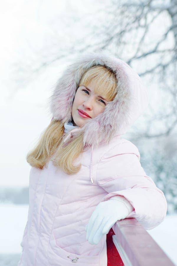La bella giovane donna bionda che porta il rivestimento rosa con un cappuccio sta sul ponte all'aperto immagini stock