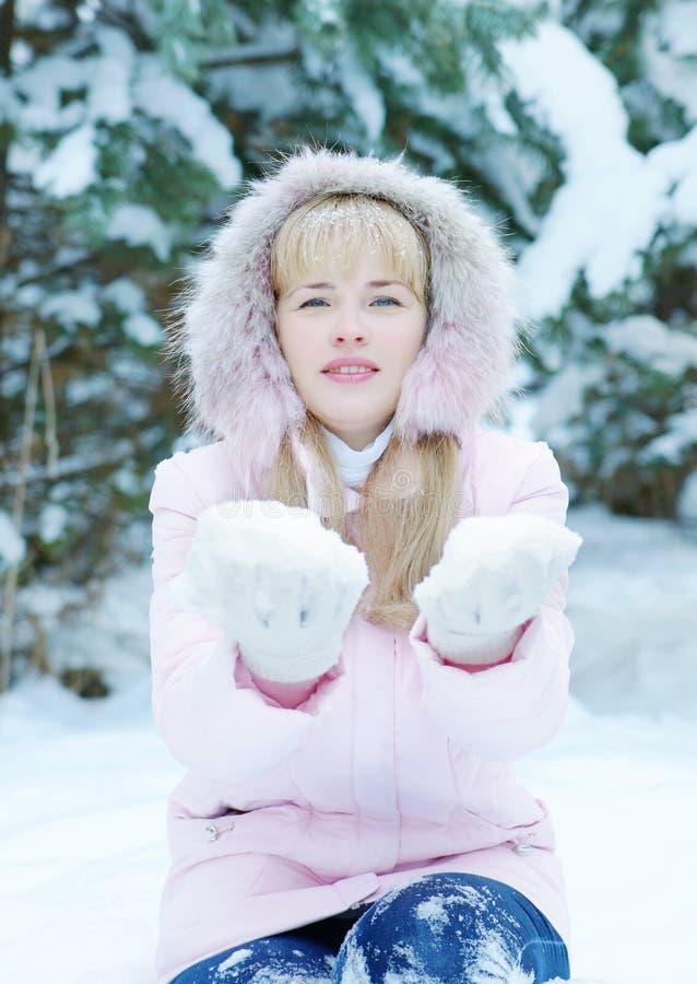 La bella giovane donna bionda che porta il rivestimento rosa con un cappuccio tiene la neve sulle sue mani fotografia stock