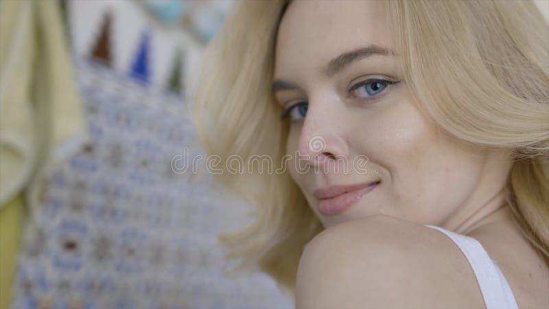 La bella giovane donna bionda con gli occhi azzurri sembra affascinante e sorrisi azione Giovane donna che esamina e che sorride  fotografia stock libera da diritti