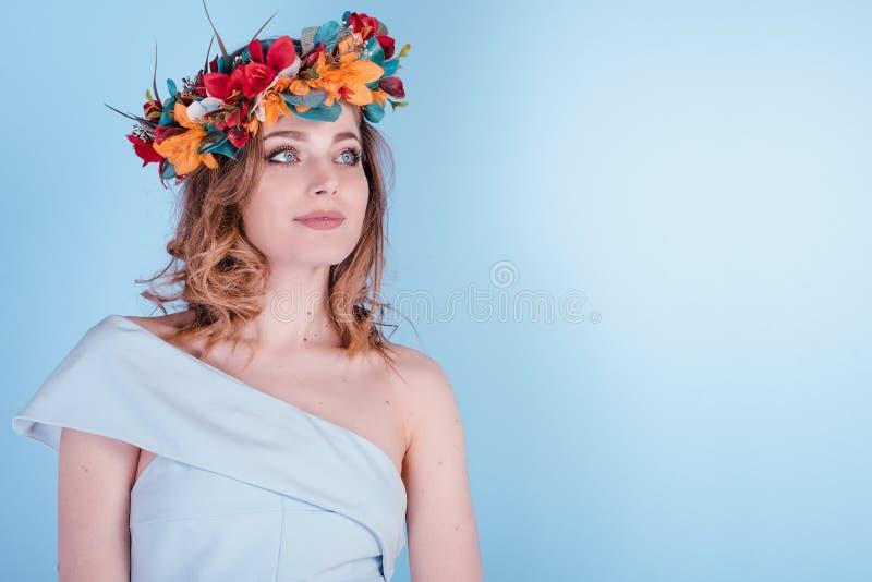 La bella giovane donna bionda con i fiori si avvolge, capelli ricci lunghi e trucco su fondo blu immagine stock