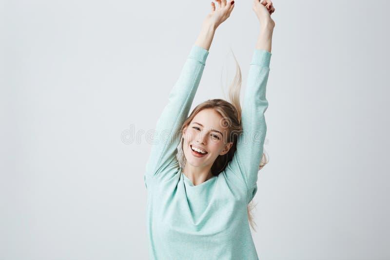 La bella giovane donna bionda nella cima blu-chiaro che allunga le armi su nell'umore allegro gradisce celebrare la vittoria larg immagini stock libere da diritti