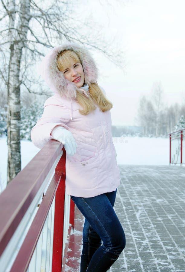 La bella giovane donna bionda si è vestita in rivestimento e blue jeans rosa immagini stock libere da diritti