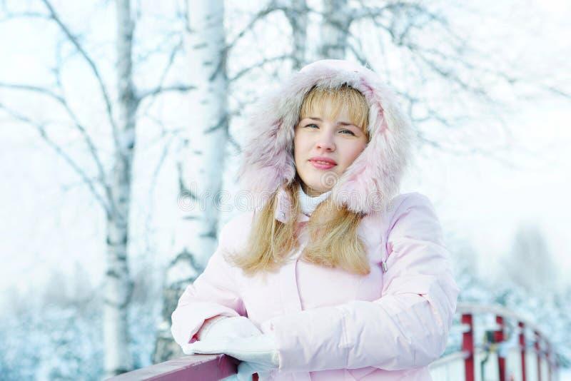 La bella giovane donna bionda si è vestita in rivestimento rosa con un cappuccio fotografia stock