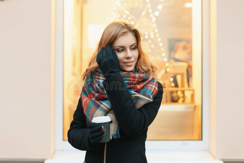 La bella giovane donna cammina nella città e nel caffè bevente fotografia stock