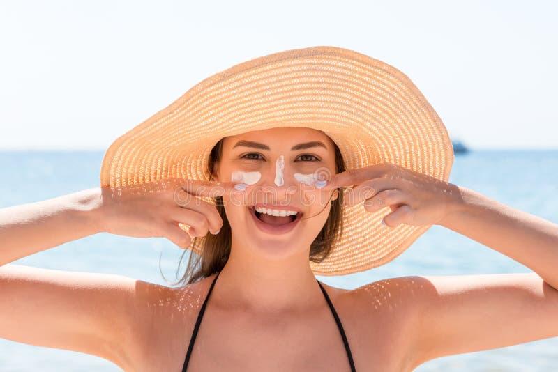 La bella giovane donna in cappello sta applicando il sunblock sotto i suoi occhi e sul suo naso come l'indiano Concetto di protez immagini stock libere da diritti