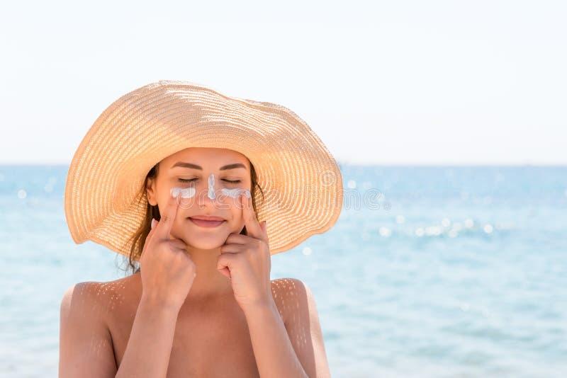 La bella giovane donna in cappello sta applicando il sunblock sotto i suoi occhi e sul suo naso come l'indiano Concetto di protez immagini stock