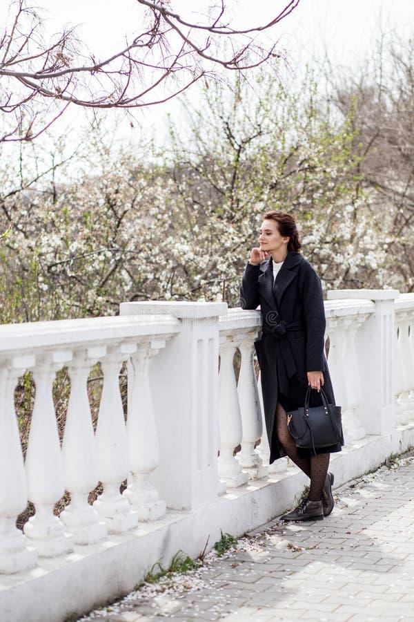 La bella giovane donna in cappotto di lana scuro nella via in primavera cronometra Fiori dei fiori della mandorla, cappotto d'ava immagine stock libera da diritti