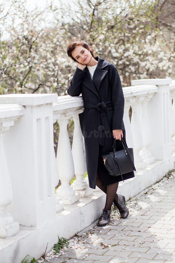La bella giovane donna in cappotto di lana scuro nella via in primavera cronometra Fiori dei fiori della mandorla, cappotto d'ava fotografia stock libera da diritti