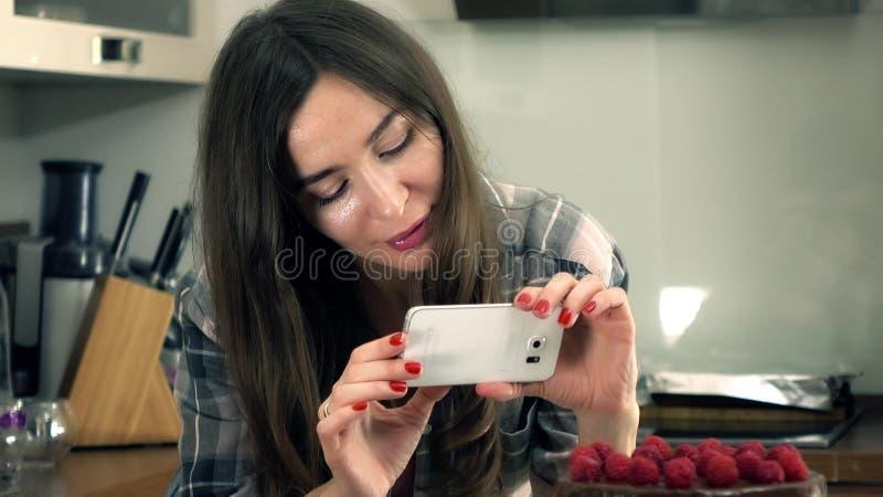 La bella giovane donna castana che fa le immagini di lei ha cucinato di recente il dolce Cottura del dilettante e concetto social fotografia stock