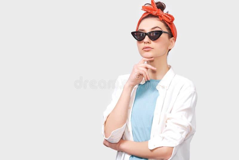 La bella giovane donna castana seria indossa gli occhiali da sole neri, la camicia bianca e la fascia rossa d'avanguardia fotografia stock libera da diritti