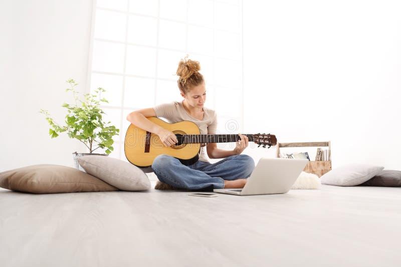La bella giovane donna che gioca la chitarra con il computer, impara al pla fotografia stock libera da diritti