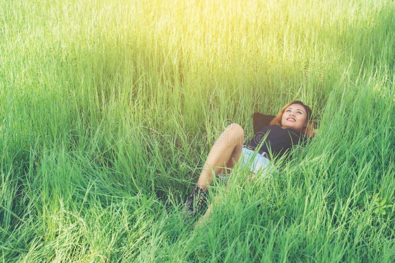 La bella giovane donna che si riposa sull'erba verde gode della vita e della h fotografia stock