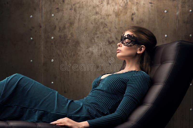 La bella giovane donna che si trova in una sedia con il suo osserva chiuso Maschera nera del pizzo immagini stock libere da diritti