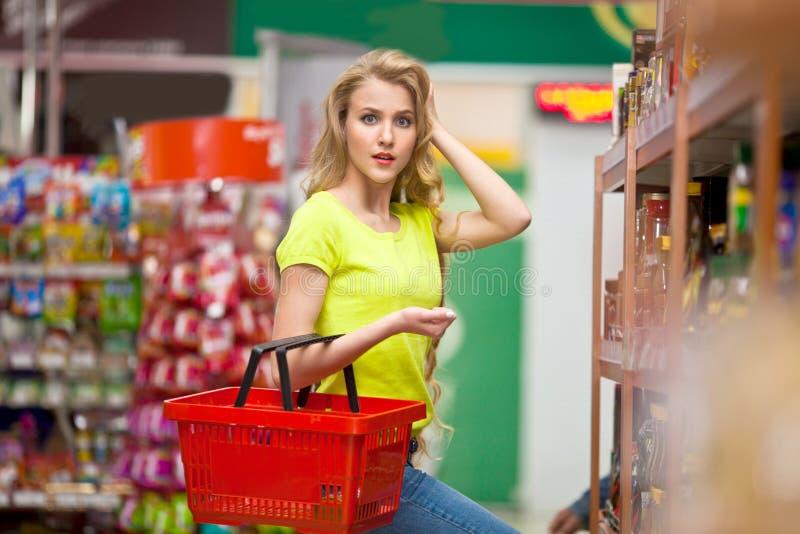 La bella giovane donna con il carrello vuoto rosso nel deposito sceglie i prodotti immagini stock