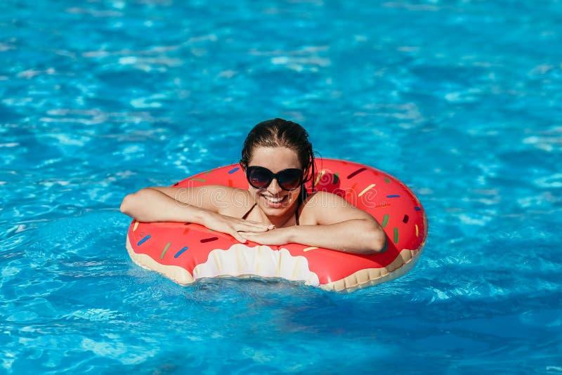 La bella giovane donna con il cerchio rosa della ciambella ha resto fotografia stock libera da diritti