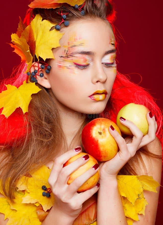 La bella giovane donna con l'autunno compone la posa nello studio più fotografia stock