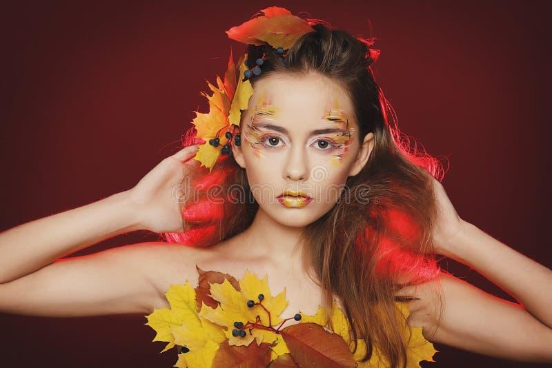La bella giovane donna con l'autunno compone la posa nello studio più fotografia stock libera da diritti