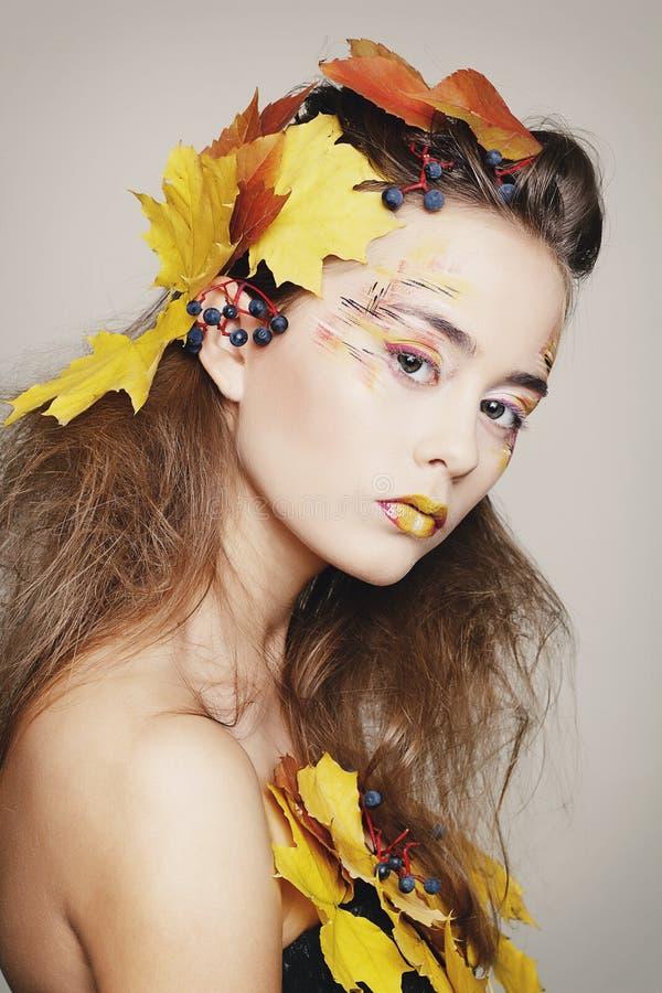 La bella giovane donna con l'autunno compone la posa nello studio più fotografie stock libere da diritti