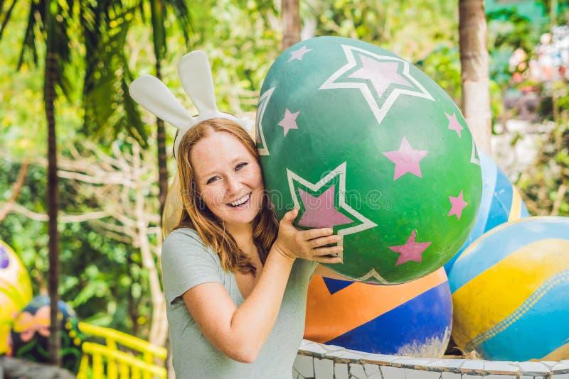 La bella giovane donna con le orecchie del coniglietto che si diverte con le uova di Pasqua tradizionali cerca, all'aperto Celebr immagini stock libere da diritti