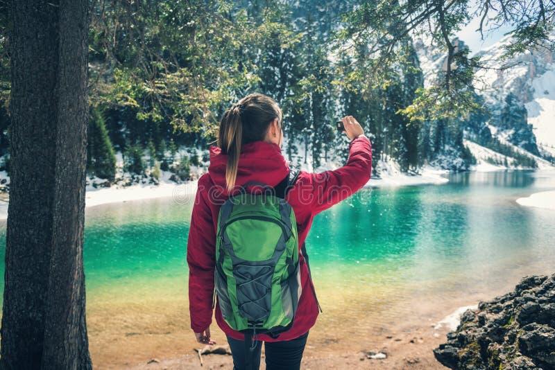 La bella giovane donna con lo zaino sta facendo il selfie sul lago immagine stock libera da diritti
