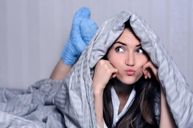 La bella giovane donna coperta dalla coperta in calzini di lana blu sta trovandosi sul letto, distoglie lo sguardo con le labbra  immagine stock