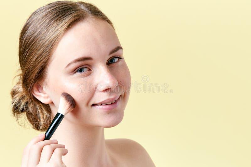 La bella giovane donna della testarossa con le lentiggini che contornano i suoi zigomi con compone la spazzola Ritratto di bellez fotografie stock
