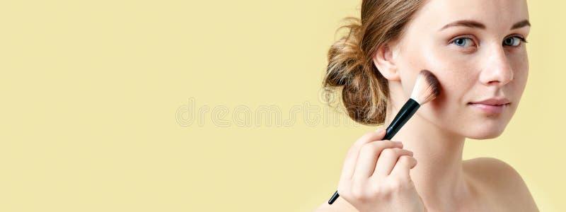 La bella giovane donna della testarossa con le lentiggini che contornano i suoi zigomi facendo uso di compone la spazzola Ritratt fotografia stock libera da diritti