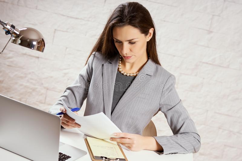 La bella giovane donna di affari sta tenendo i documenti fotografie stock libere da diritti