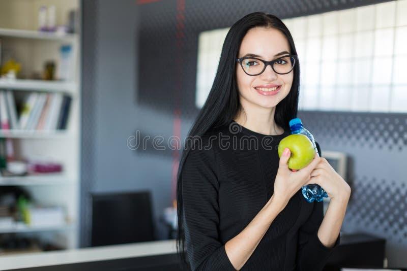 La bella giovane donna di affari in vestito nero ed i vetri si siedono sulla tavola nell'ufficio e tengono la mela e la bottiglia immagini stock libere da diritti