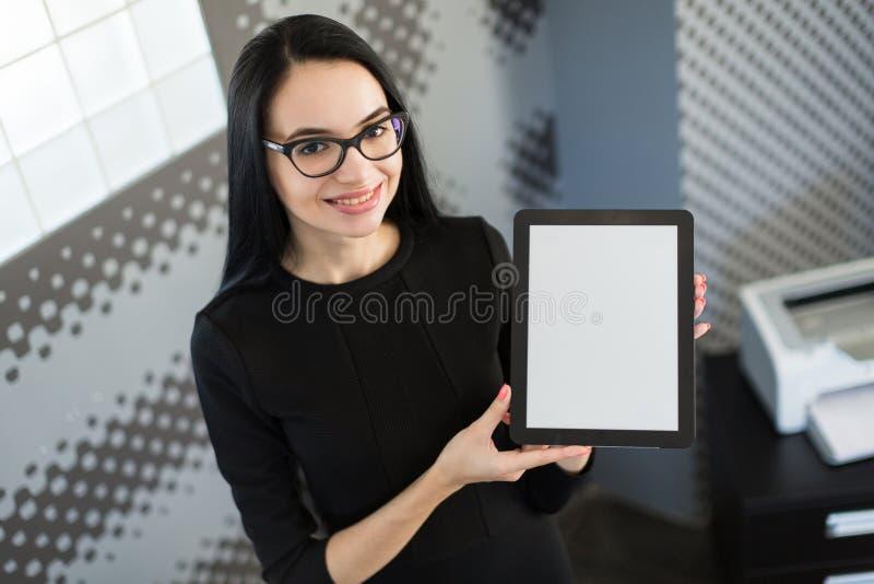 La bella giovane donna di affari in vestito nero ed i vetri tengono la cartella di carta e mostrano la compressa fotografie stock libere da diritti