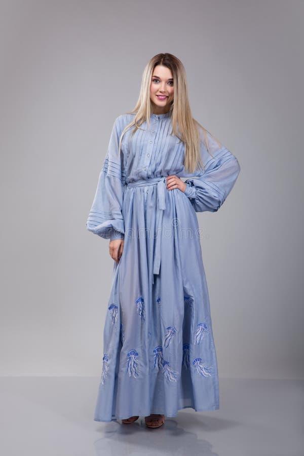 La bella giovane donna dresseed in vestito ricamato blu lungo sul fondo grigio dello studio immagine stock