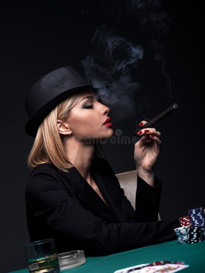 La bella giovane donna fuma un sigaro durante il gioco del poker fotografia stock libera da diritti