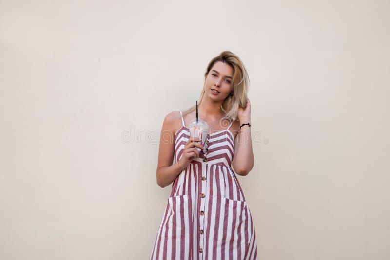 La bella giovane donna graziosa in un vestito a strisce dall'estate lunga rosa con un cocktail dolce fresco in sue mani sta stand immagini stock