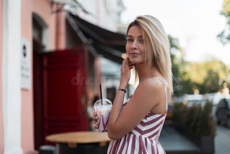 La bella giovane donna graziosa in un vestito a strisce rosa d'avanguardia sta con una bevanda lattea saporita in mani vicino ad  fotografia stock