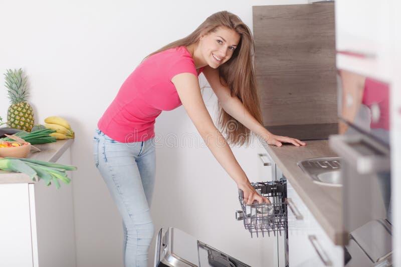 La bella giovane donna ha composto i piatti nella lavastoviglie immagini stock libere da diritti