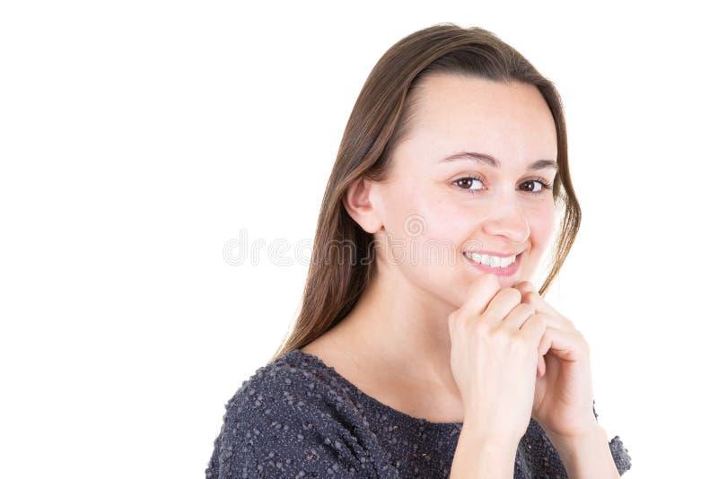 La bella giovane donna ha isolato il fondo bianco che sembra sicuro con la mano di sorriso sollevata sul mento fotografie stock