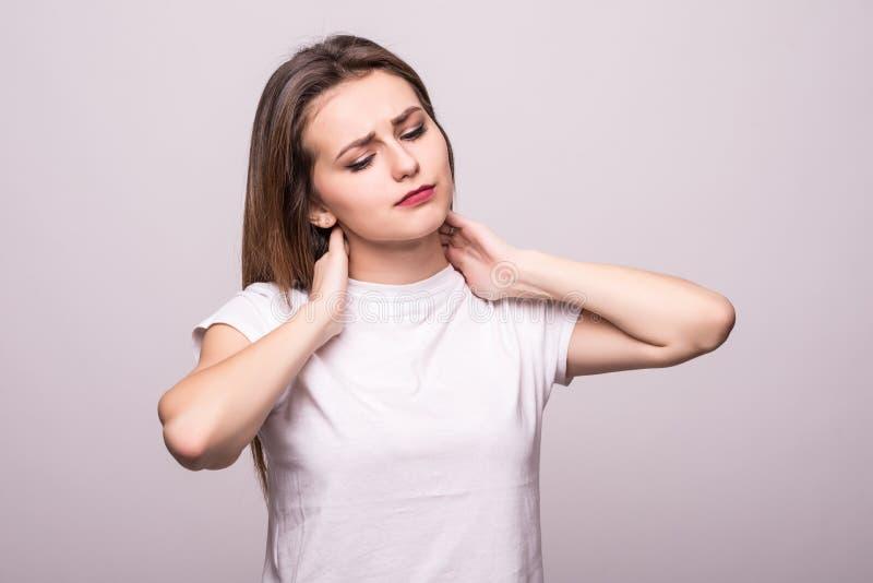 La bella giovane donna ha un dolore al collo isolata su fondo grigio fotografie stock