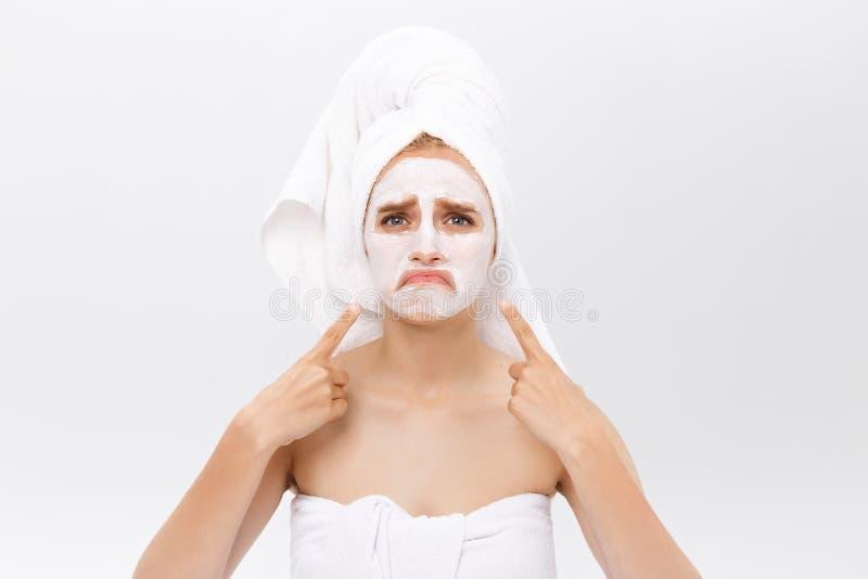 La bella giovane donna infelice con la maschera di protezione bianca dell'argilla fa la terapia dell'acne, indossa l'asciugamano  immagini stock libere da diritti